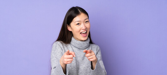 Young asian woman over isolated background surprised and pointing front