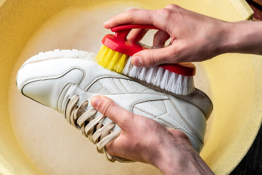 Sneakers in a wash basin with soapy water. Washing the dirty sneakers, cleaning the shoes.