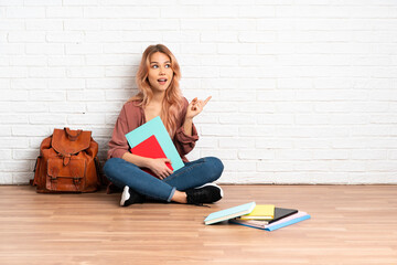 Teenager student woman with pink hair sitting on the floor at indoors intending to realizes the solution while lifting a finger up