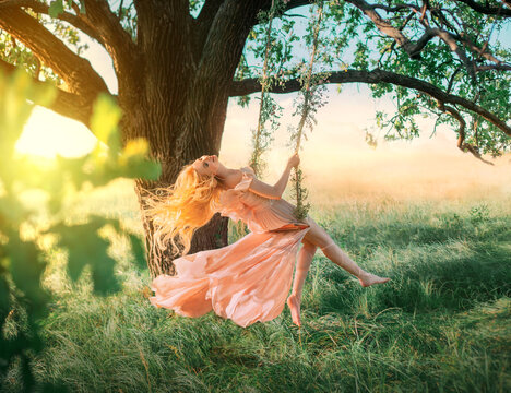Beautiful happy woman nymph sitting on swings. Magical fantasy swing. princess long peach color orange silk vintage dress fluttering wind. blond hair fly in motion. Tree sunshine green grass forest