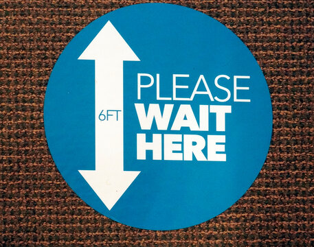 Round social distancing PLEASE WAIT HERE sign secured to interior business carpet.
