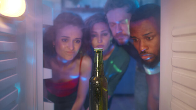 Sad diverse friends look at last beer bottle in fridge