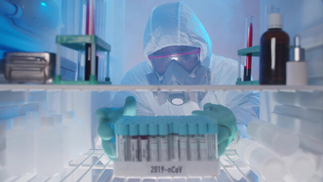 Lab technician checking blood samples in fridge for later use
