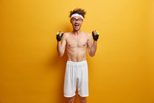 Funny positive skinny man raises hands with clenched fists, feels very happy and motivated, wears white headband, sport gloves and shorts, poses against vivid yellow background, ready to train muscles