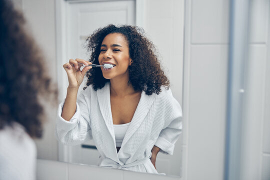 Pleased curly-headed pretty lady brushing her teeth