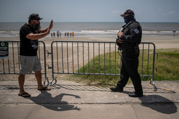 Man asks police to keep distance during protest of closed beaches on 4th of July amid the global outbreak of the coronavirus disease in Galveston, Texas