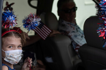 Girl seen through car window during 4th of July parade amid the global outbreak of the coronavirus disease in Galveston, Texas
