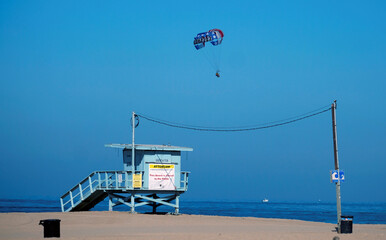 A parasail flies above a closed beach during the outbreak of the coronavirus disease (COVID-19) at Venice Beach in Los Angeles