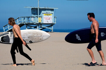 Surfers walk past a beach closed sign hanging on a lifeguard booth during the outbreak of the coronavirus disease (COVID-19) at Venice Beach in Los Angeles