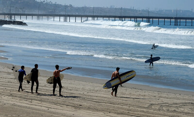 Surfers walk to the water during the outbreak of the coronavirus disease (COVID-19) at Venice Beach in Los Angeles