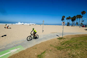 A bicyclist ride along a bike path during the outbreak of the coronavirus disease (COVID-19) at Venice Beach in Los Angeles