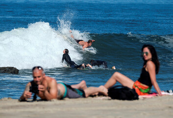 People surf during the outbreak of the coronavirus disease (COVID-19) at Venice Beach in Los Angeles