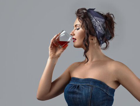 Beautiful young woman in a denim jumpsuit drinks whiskey.