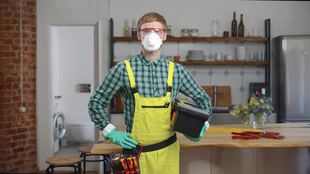 Portrait of young plumber in facial mask over kitchen background