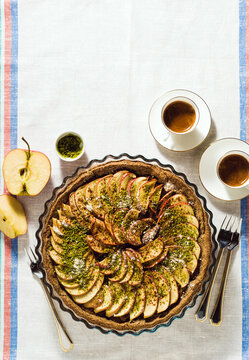 italian apple pie crostata with pistachio crumbs on the table with a white tablecloth and cups of coffee espresso