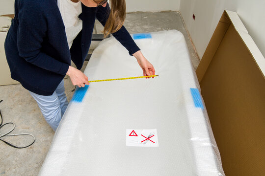 Young architect woman measuring with yellow tape the size of a new boxed packed luxury bath