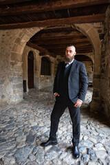 Man in dark elegant suit posing under the arcades