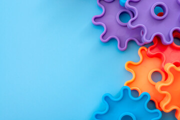 Teamwork and solidarity concept with photograph of connected colorful plastic toy gears with each gear a different color isolated on blue background with copy space