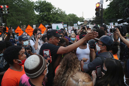 Protesters argue over burning American flags and leaflets with the flag, even as other protesters disagreed with the act, during a protest against racial inequality and police violence near Black Lives Matter Plaza