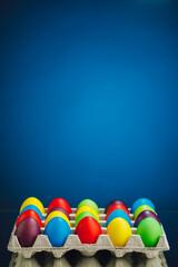 Easter festive multicolor eggs carton, blue background