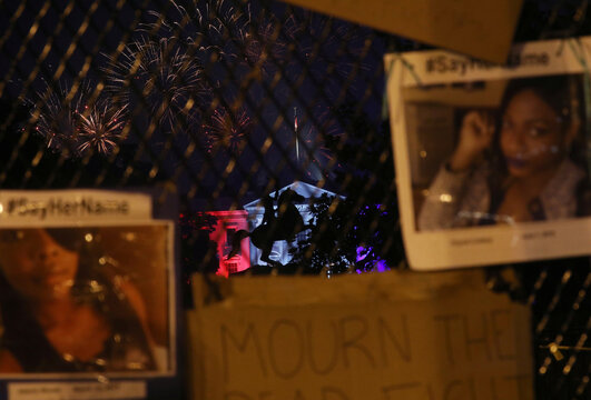 Fireworks from the National Mall are seen through a fence around Lafayette square displayed with tribute photos of Chynal Lindsey and Alteria Woods, during Fourth of July holiday, in Washington
