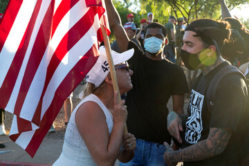 Black Lives Matter protesters interact with demonstrators against restrictions to prevent the spread of the coronavirus disease (COVID-19) in Phoenix