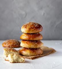 Fototapeta Burger buns in stack, freshly baked, sprinkled with sesame seeds obraz