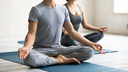 Close up focus on unrecognizable young strong athletic guy sitting on floor yoga mat in lotus position with folded hands in mudra gesture, deeply meditating after finishing workout at group class.