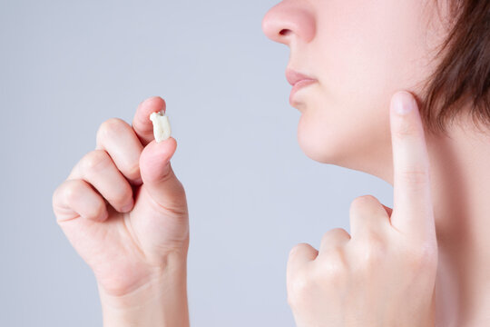 Wisdom tooth extraction, woman suffering from a toothache on gray background