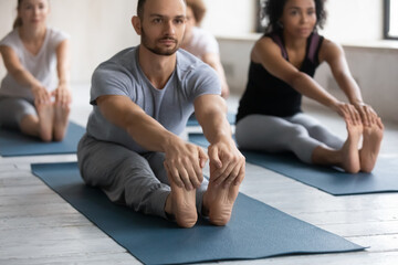 Concentrated young multiracial people practicing seated forward bend pose on floor mat in modern yoga interior, diverse beginners students stretching legs hamstring muscles together at group class.