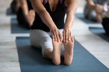 Close up front view young barefoot biracial woman sitting on yoga mat, touching feet with hands,...