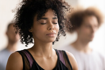 Fototapeta Head shot close up young peaceful attractive curly hair african american woman breathing fresh air, enjoying deep meditation with closed eyes, relaxing after yoga class workout in sport club. obraz
