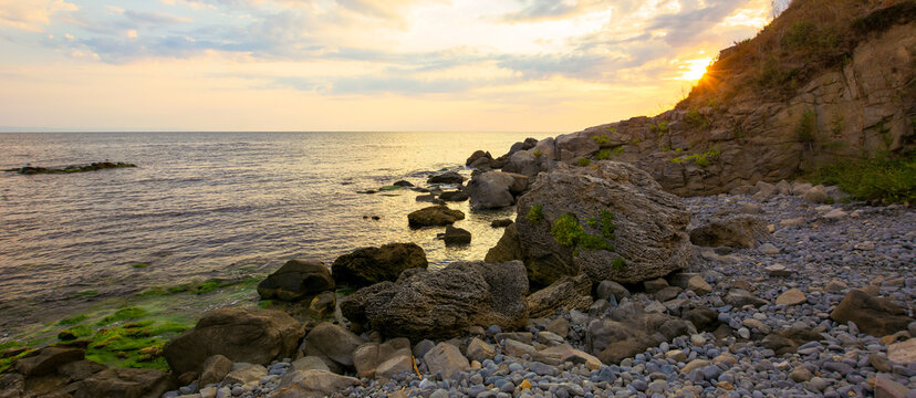 sea beach with pebbles and rocks. beautiful landscape with clouds on the sky at sunrise. wide panoramic view of a bay