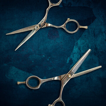 Barber scissors on a dark blue, grunge background. Beauty and fashion. Barbershop.