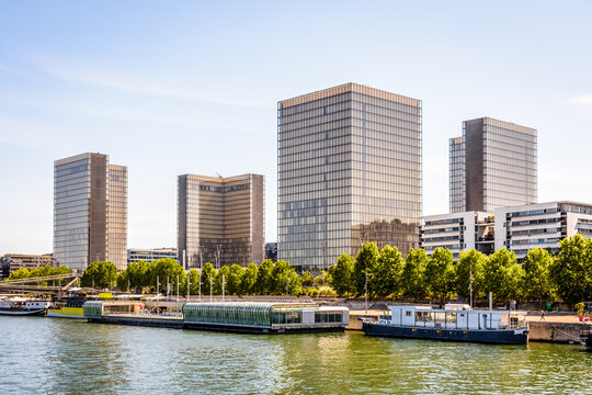 Paris, France - June 23, 2020: General view of the four towers of the Francois Mitterrand national library on the banks of the Seine with the Josephine Baker floating swimming pool in the foreground.