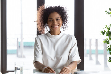 Happy millennial african American female employee sit at desk in office talk on video call with...