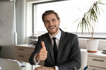 Portrait of excited young Caucasian businessman sit at desk in office show thumb up give recommendation, overjoyed male employee make like gesture advice recommend good quality company service