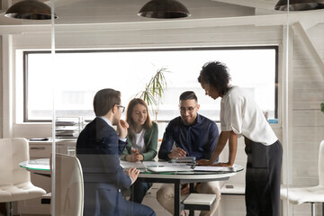 Smiling multiracial young businesspeople sit at table in boardroom discuss paperwork company...