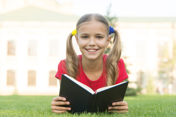 Open your imagination, read. Happy kid read book on green grass. Developing imagination. Childhood imagination. Imagination and fantasy. Cognitive reading skills. Summer reading. Become imaginative Wall mural