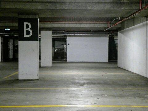 Interior of empty industrial looking indoor parking lot inside of parking garage