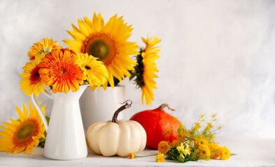 Fototapeta Beautiful autumn still life with bouquet of red and yellow flowers in white vases and white and orange pumpkins on wooden table, front view. Autumn concept with pumpkins and flowers. obraz