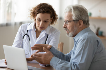 Young female doctor consult elderly male patient in hospital, discuss healthcare insurance on...
