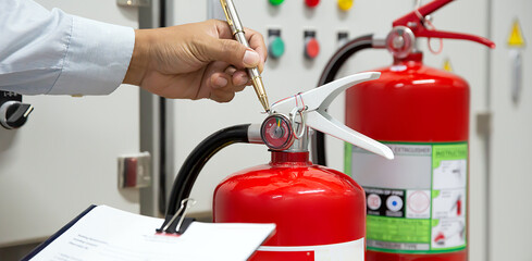 Fire fighter are checking fire extinguishers tank in the building concepts of fire prevention...