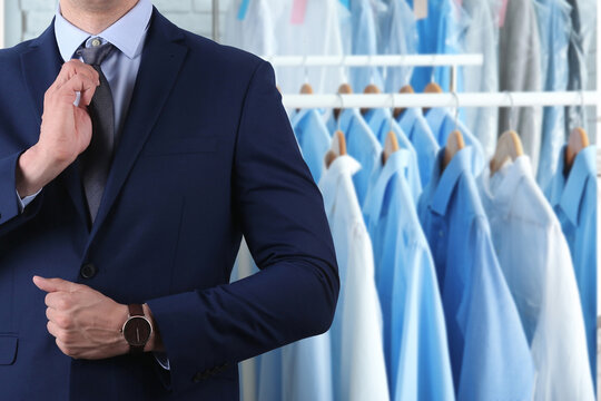 Businessman and rack with clean clothes at dry-cleaner's, closeup. Space for text