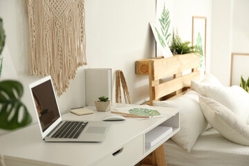 Stylish room interior with workplace and bed