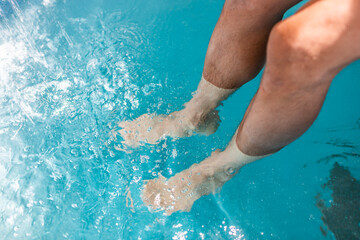 Young man legs closeup sitting in Japanese spa by stone pool dipping feet in colorful blue water and waterfall in Japan onsen