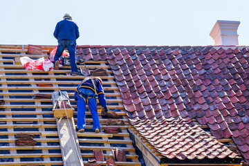 Fototapeta roof repair of a historic house and replacement of clay tiles obraz