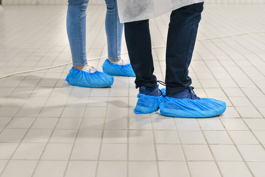 Close up on feet of unknown man and woman wearing overshoes - Blue medical shoe covers for protection on floor in hospital - Medical antibacterial plastic disposable pull on slippers hygiene standard