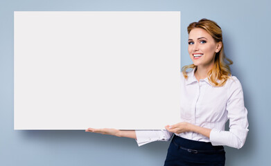 Happy amazed business woman in white confident clothing showing blank banner signboard. Success in business and advertising concept. Copy space empty place for some text or imaginary.