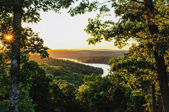 Peaking thru the trees as the sun is starting to rise over the mountains and a cove on Norfork Lake in Mountain Home, Arkansas